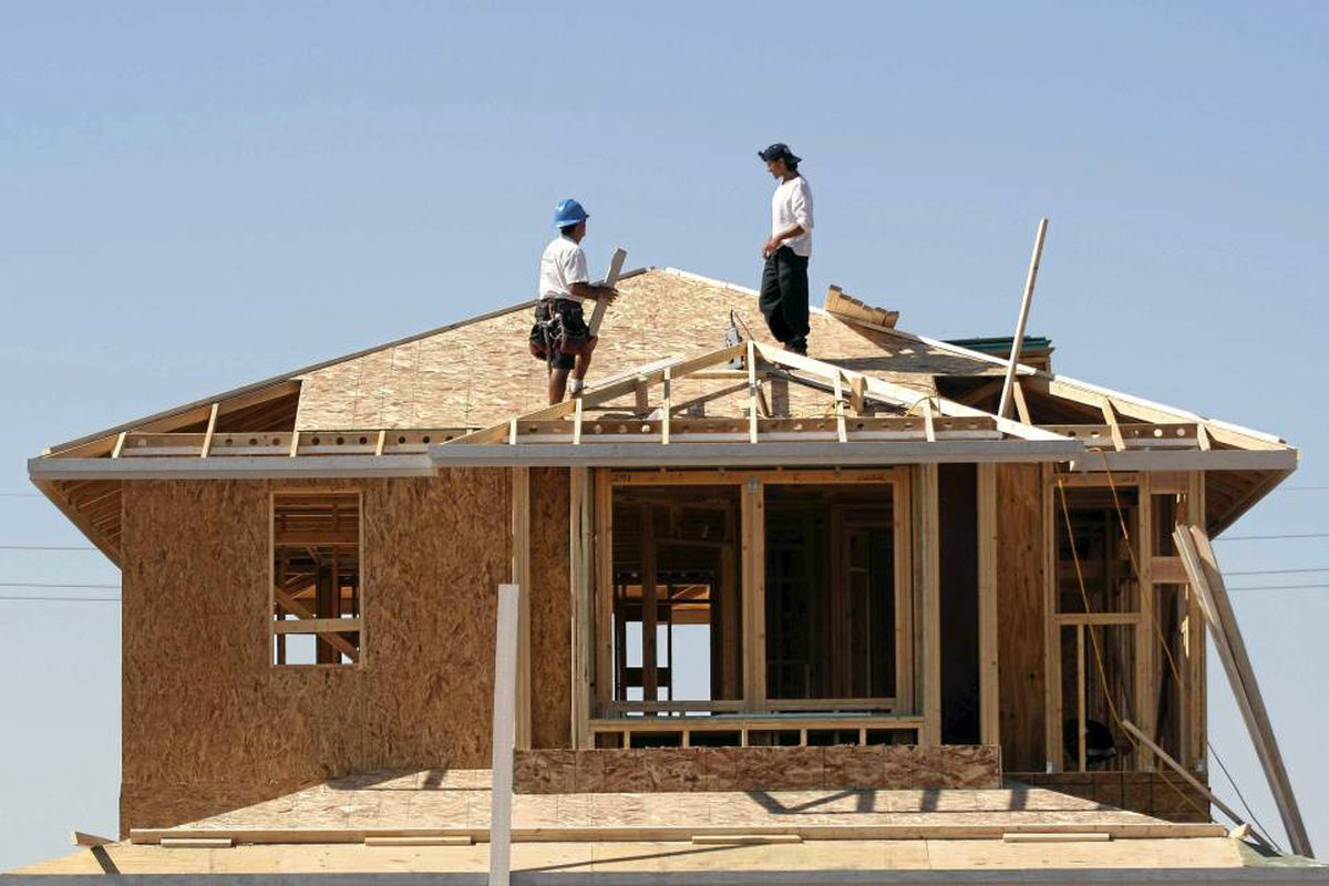 Workers build a house for developer KB Home in Gilbert, Ariz.
