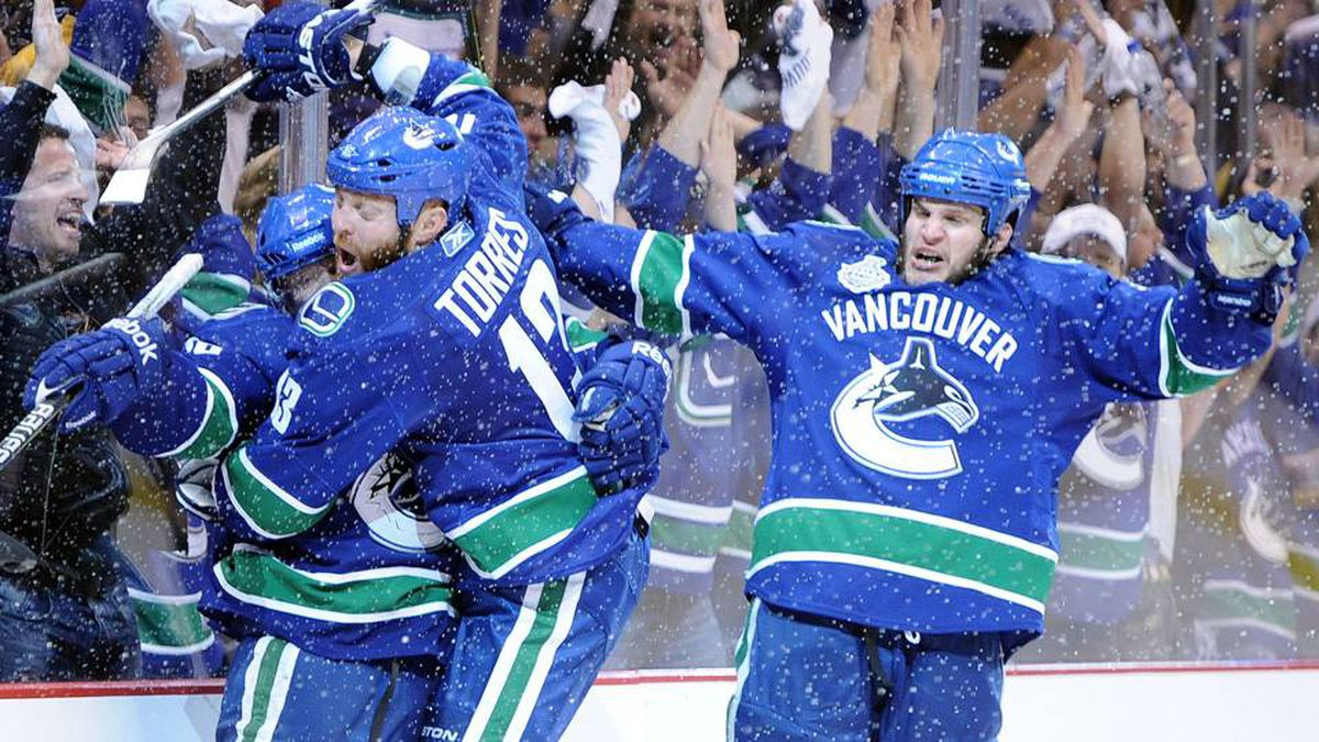 Raffi Torres of the Vancouver Canucks celebrates with his teammates Victor Oreskovich and Kevin Bieksa after a goal late in the third period.