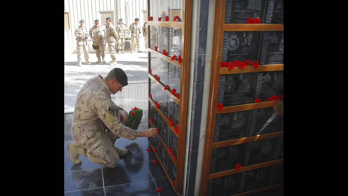 A Canadian soldier places a poppy on a monument at Kandahar Airfield to Canadian soldiers killed in Afghanistan during a Remembrance Day ceremony.