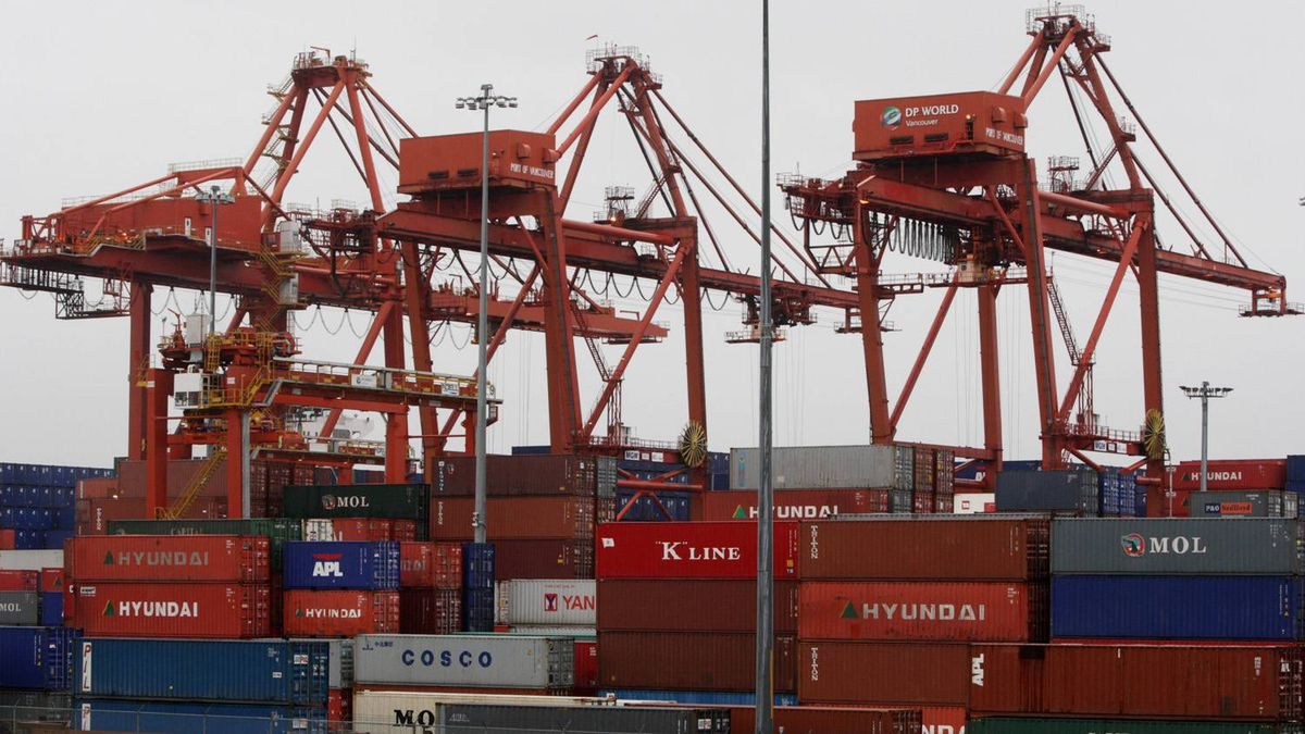 Cargo containers are stacked up as three cranes used to load and unload them from cargo ships tower above at the Port of Vancouver in Vancouver, B.C.
