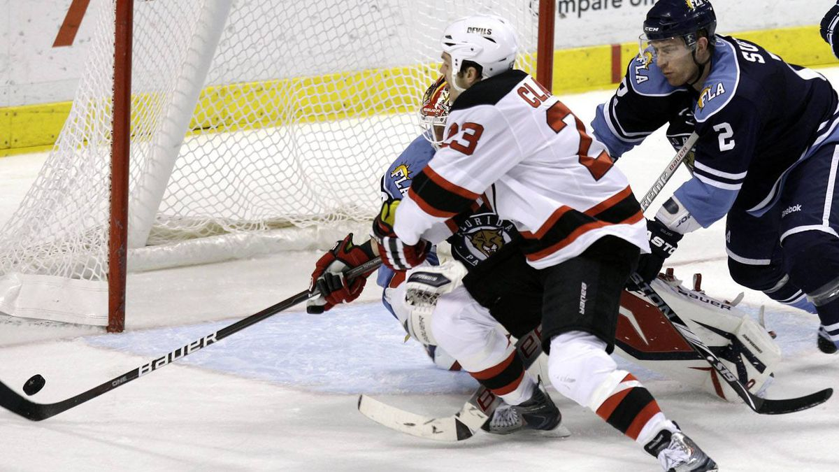 New Jersey Devils' David Clarkson (23) scores the first goal of an NHL hockey game as he skates around Florida Panthers' Alexander Sulzer (2) and goalie Tomas Vokoun (obscured) during the second period in Sunrise, Fla. Sunday, Feb. 27, 2011. The Devils won 2-1. (AP Photo/J Pat Carter)