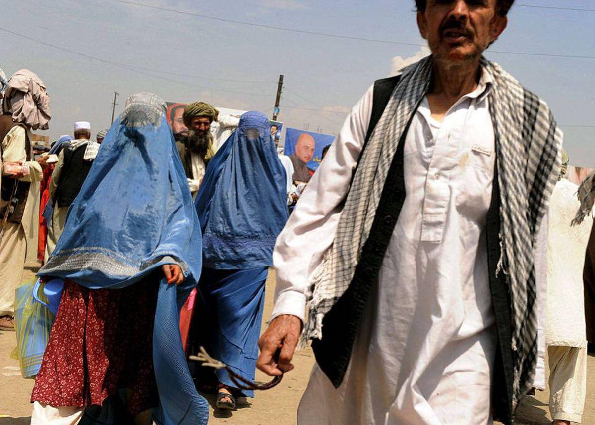 Afghan pedestrians walk on a street in Kabul on August 10, 2010.