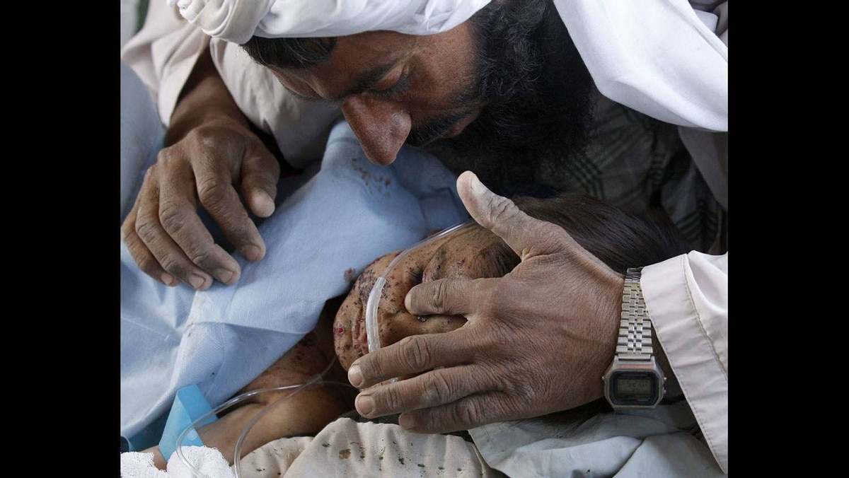 A father wipes a tear away from his child's face during a Medevac mission in southern Afghanistan's Helmand province, November 13, 2010.