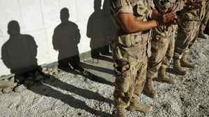 The shadows of Canadian troops are cast on a memorial for fallen soldiers as they applaud a speech by Defence Minister Peter MacKay at Kandahar Air Field on November 5, 2007.