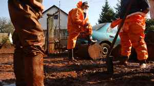 Residents take a break during clean up works in the flooded village of Devecser, 150 km west of Budapest October 11, 2010.