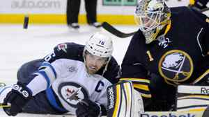 Buffalo Sabres goalie Jhonas Enroth (1) keeps an eye on the puck with Winnipeg Jets left wing Andrew Ladd (L) during the first period of their NHL hockey game in Buffalo, New York January 7, 2012. REUTERS/Doug Benz