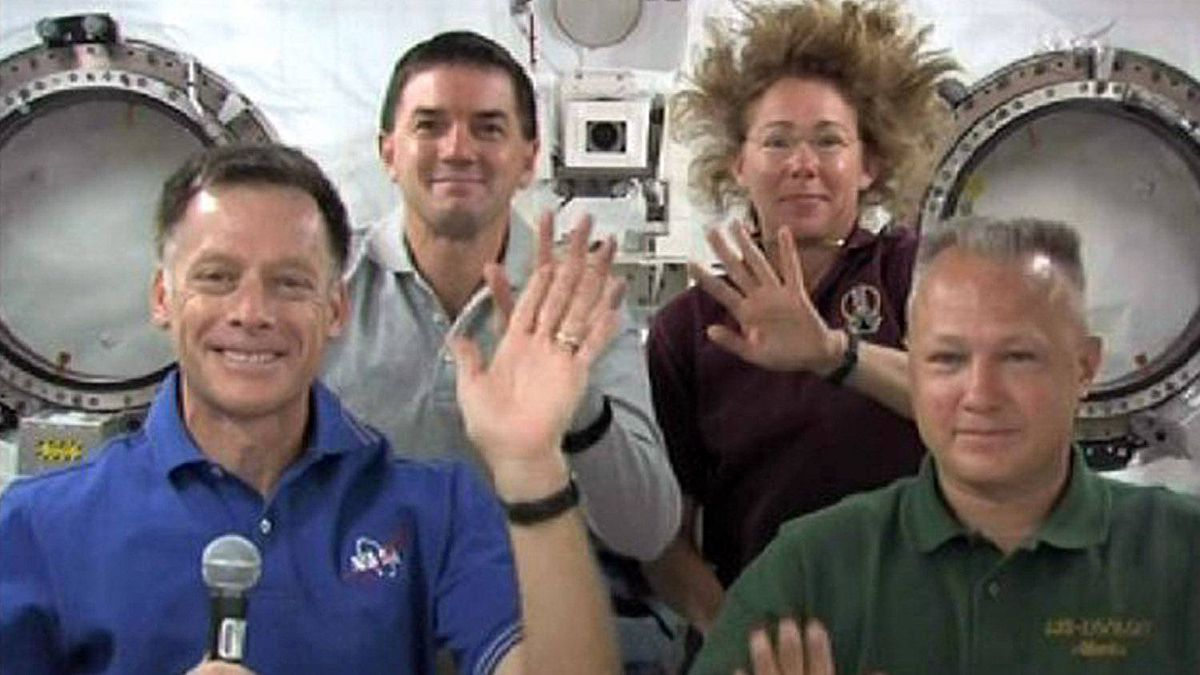 Space shuttle Atlantis astronauts (L-R) Commander Chris Ferguson, Rex Walheim, Sandy Mangus and Pilot Doug Hurley wave during a crew news conference from the International Space Station.