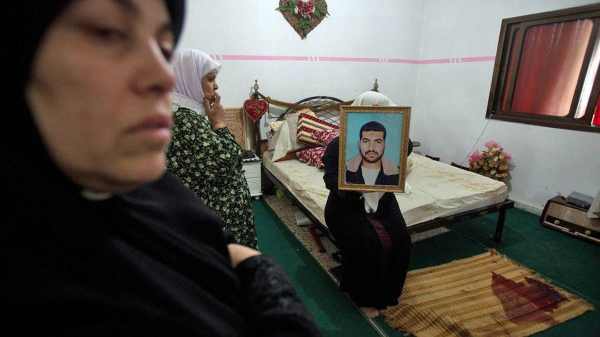 Latify Abu Shelbayeh holds a portrait of her husband Iyad, a Hamas member, in the bedroom of their home during his funeral in the Nour Shams refugee camp near the West Bank town of Tulkarm on Sept. 17, 2010.