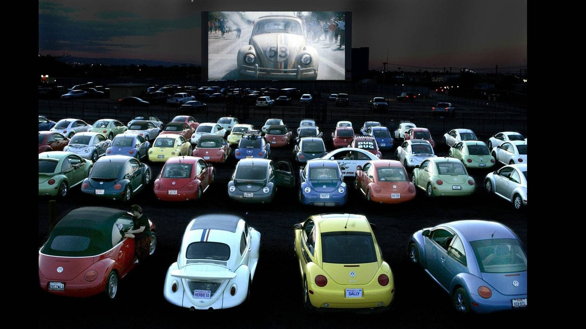 A fleet of first-generation new Beetles line up in front of a screen showing Disney's famous Love Bug movie race car. In the foreground is a Herbie-replica Beetle with a Porsche-style whale-tail spoiler.