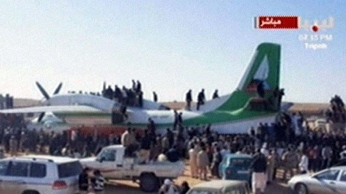 An image grab taken from the Libya Al-Ahrar TV station on November 19, 2011 shows Libyan fighters climbing on the aircraft that brought Seif al-Islam, the fugitive son of ousted and killed Libyan leader Moamer Kadhafi, after it landed at an air strip in the town of Zintan, following Islam's arrest in southern Libya.