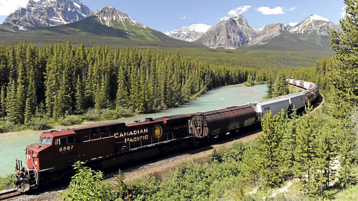A CPR (Canadian Pacific Railway) freight train runs along the Bow River and distant Rocky Mountains on the CPR main line near Lake Louise, Alberta. The Canadian Press Images/Larry MacDougal
