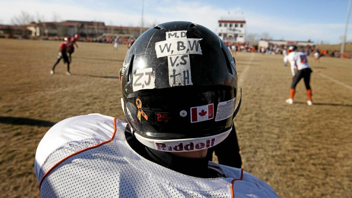 Warriors running back Marcus Cooper wears the initials of his teammates Vincent Stover 16, Matt Deller, 16, Walter Borden - Wilkins 15, and Tanner Hildebrand, 15, who were killed and Zach Judd who was injured in a car accident in Grande Prairie on Saturday, October 22, 2011.