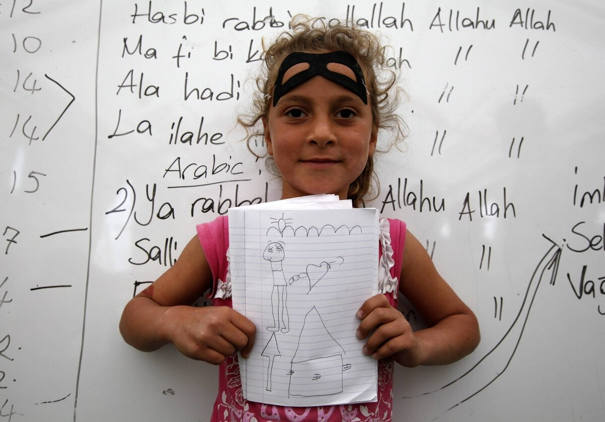 Meriya Senkar, 10, a Syrian refugee, shows a drawing of her dream home during a class at a school for refugee children at Boynuyogun refugee camp in Hatay province near the Turkish-Syrian border.
