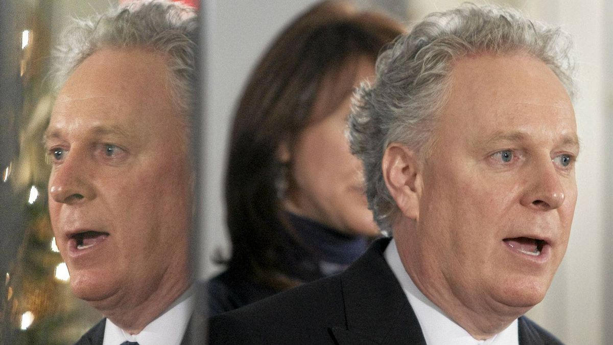 Quebec Premier Jean Charest is reflected on a television screen as he responds to questions at the news conference marking the end of the fall session Friday, December 10, 2010, at the legislature in Quebec City.
