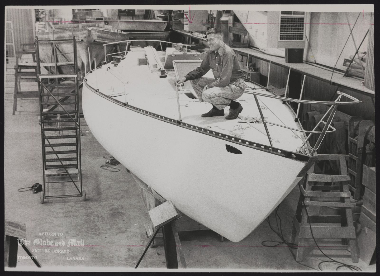 C AND C YACHTS LIMITED George Cuthbertson, president of C and C Yachts Ltd., inspects hull of new craft at Oakville plant.