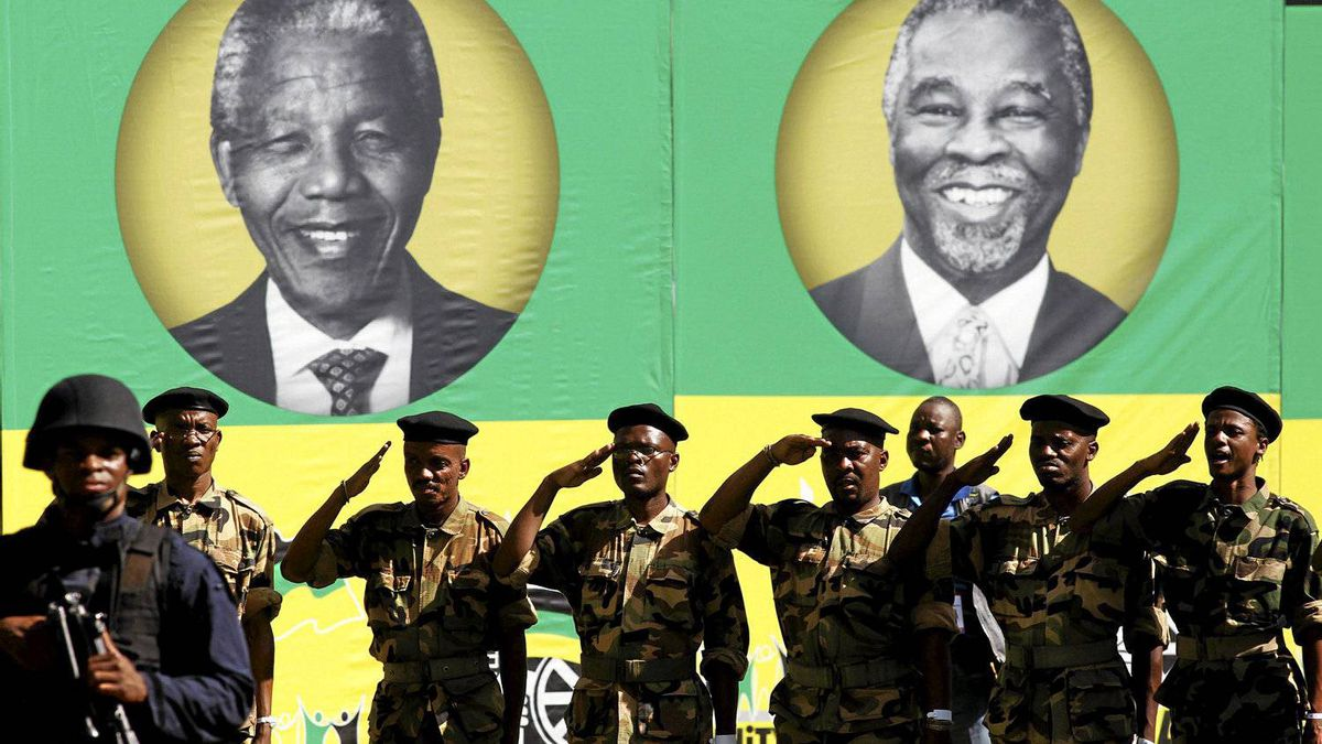 Members of the Umkhonto We Sizwe Military Veterans Association (MKMVA) salute in front of posters of former presidents of the African National Congress (ANC), Nelson Mandela (L) and Thabo Mbeki, during the ANC's centenary celebration in Bloemfontein Jan. 8, 2012.