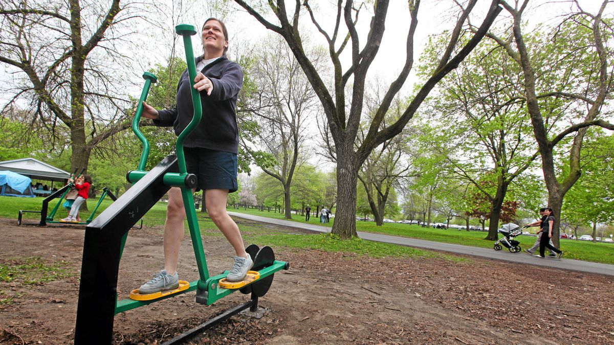Beata Reitner tries out an elliptical machine at an outdoor workout station alongside the Woodbine Beach playground in Toronto Monday May 23, 2011.