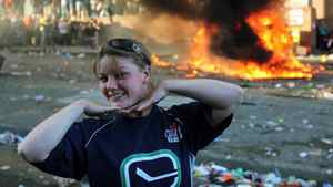 A Canucks fan poses for photos in front of an overturned pickup truck as it burns in downtown Vancouver after Game 7 of Stanley Cup finals on June 15, 2011.