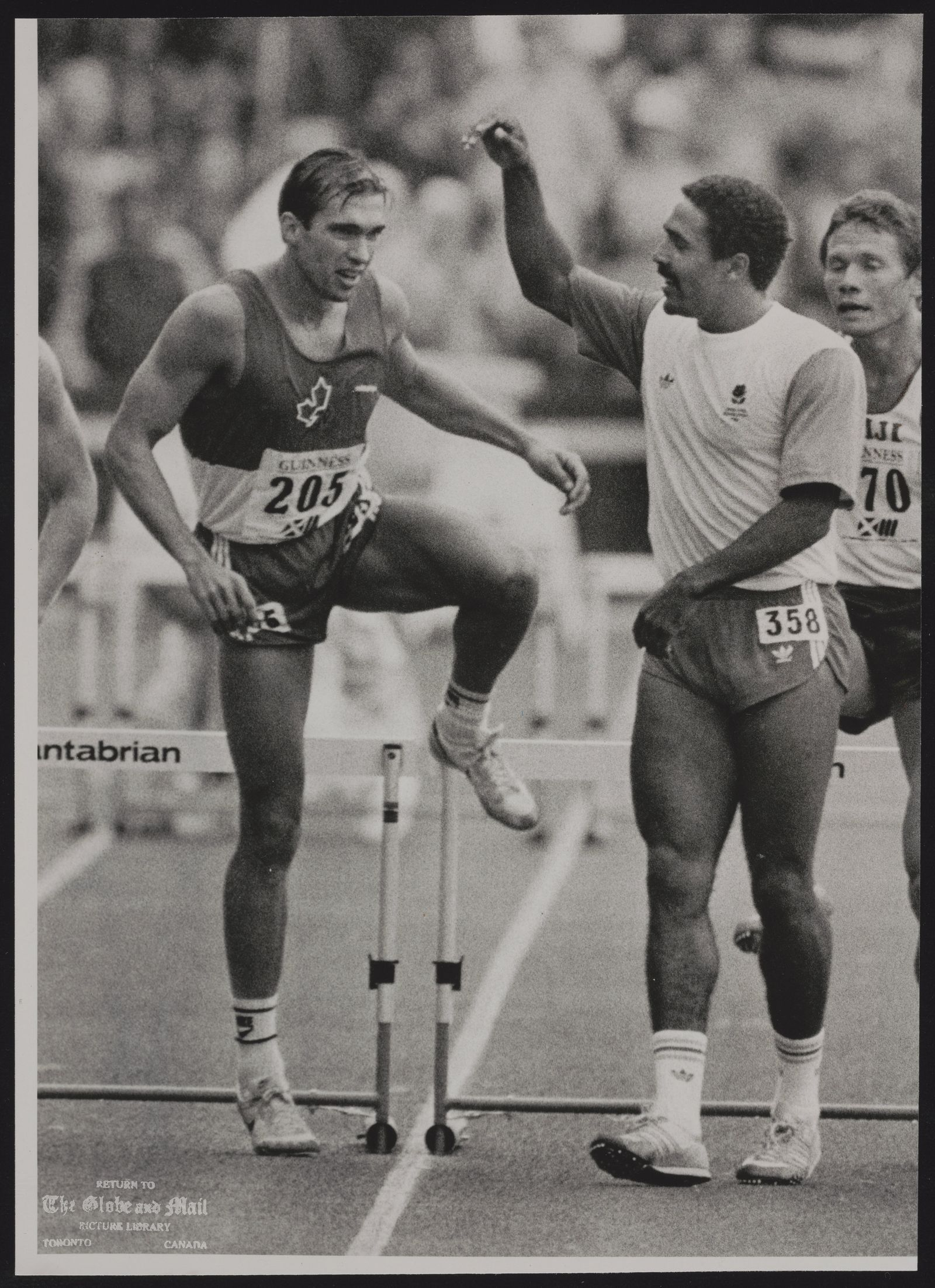 COMMONWEALTH GAMES EDINBURGH 1986 EDI21:SPECIAL FOR TORONTO GLOBE AND MAIL, CANADA EDINBURG, SCOTLAND, JULY 28,- Commonwealth Games decathlon Gold medallist Daley Thompson is watched by silver medallist Dave Steen of Canada during the victory lap of honour at Meadowbank Stadium