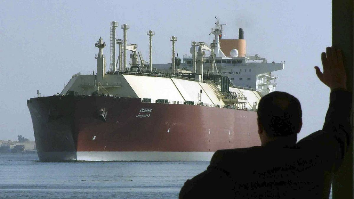 A man looks as an LNG tanker crosses through the Suez Canal.
