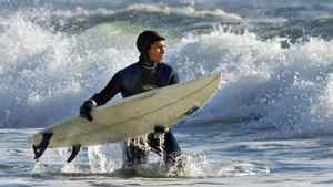 A surfer takes to the waves at Lawrencetown Beach, east of Halifax, on Dec.30, 2001.