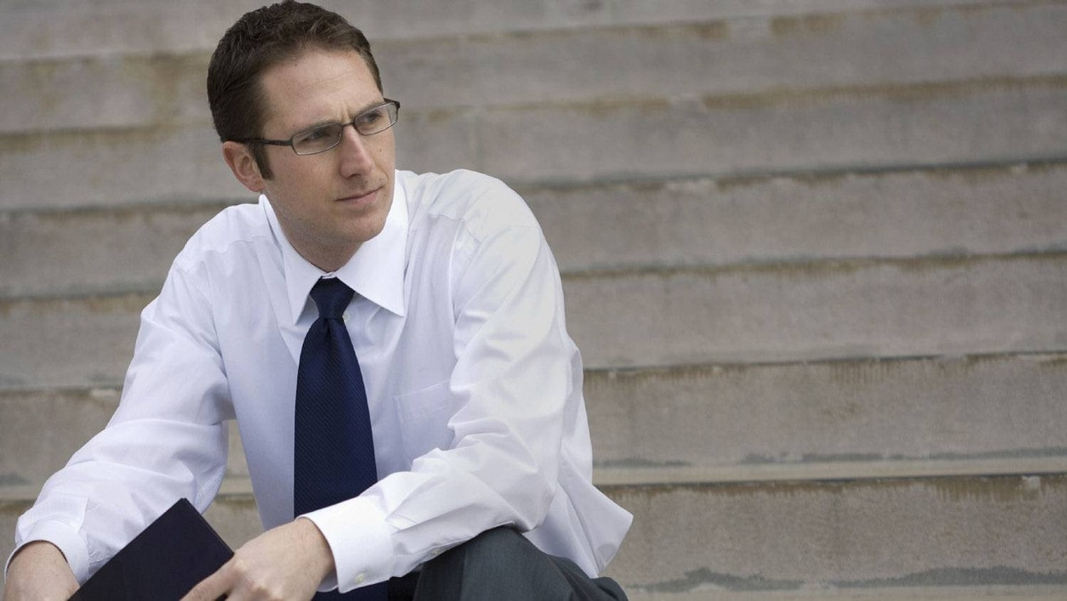 Young businessman sits on steps.