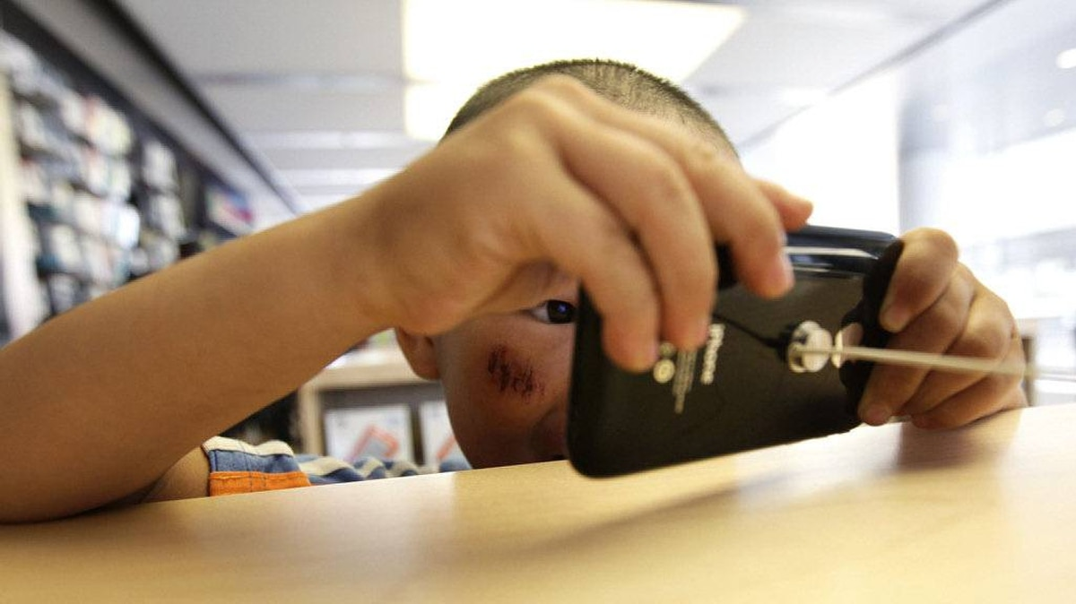 A 5-year-old boy plays games on an iPhone in the company's flagship store in Beijing's Sanlitun Area, which is one of four official Apple stores in China, July 22, 2011.
