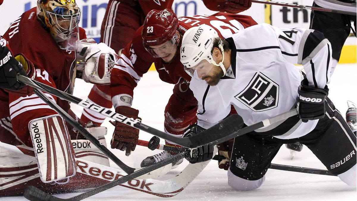Los Angeles Kings' Justin Williams (14) battles with Phoenix Coyotes' Oliver Ekman-Larsson (23), of Sweden, and goalie Mike Smith, left, for the puck in the second period during Game 5 of the NHL hockey Stanley Cup Western Conference finals, Tuesday, May 22, 2012, in Glendale, Ariz. (AP Photo/Ross D. Franklin)