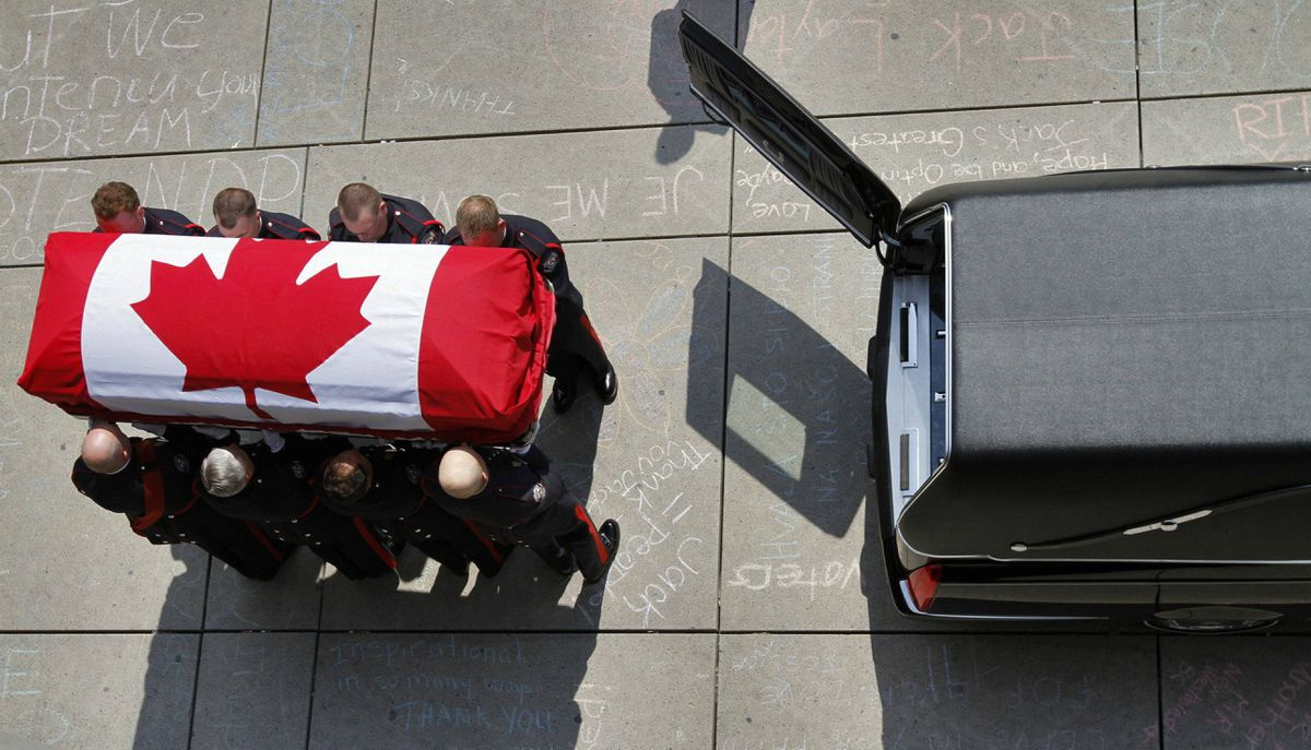 A group of police officers carry the coffin of former NDP leader Jack Layton outside of Toronto City Hall.
