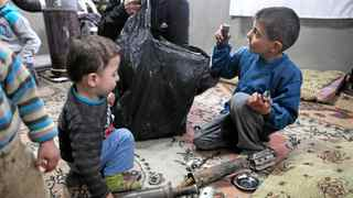 The children of Abdel Salam, a Syrian rebel brigade commander, play with the fragments of rocket-propelled grenades recently fired at their father's men.