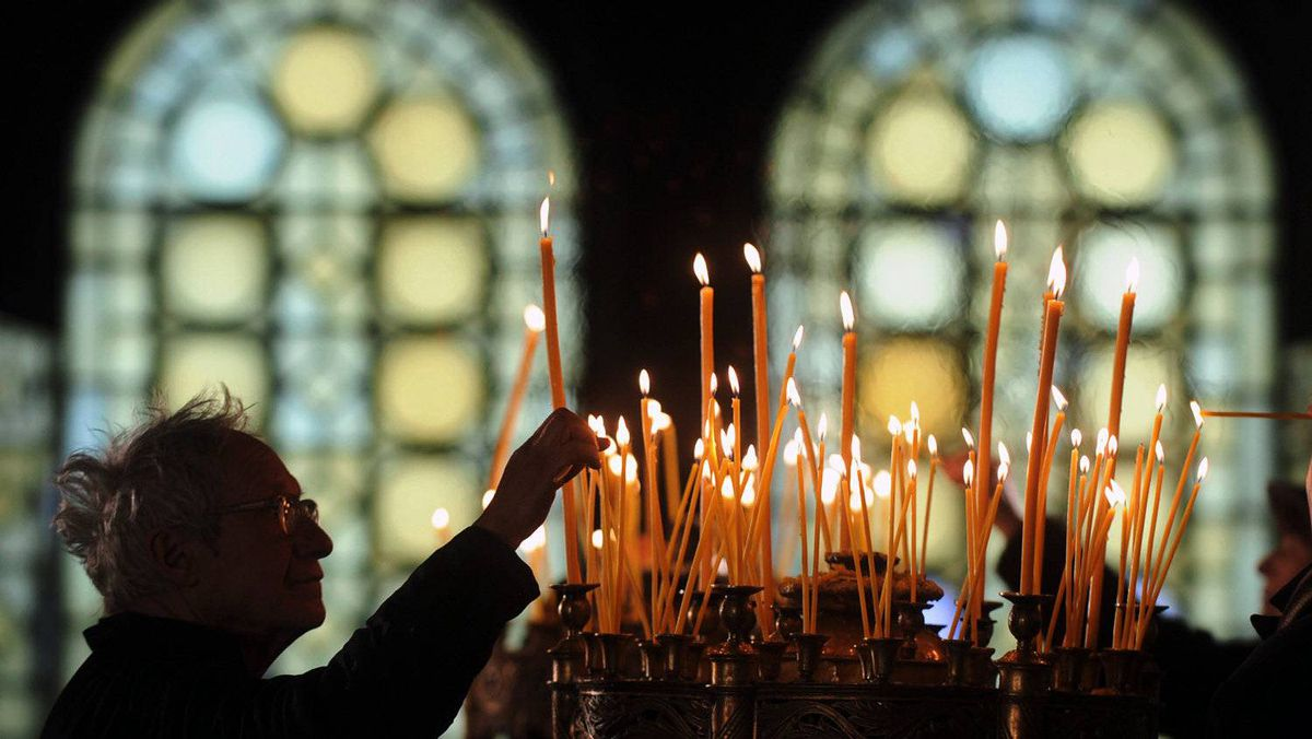 A man lights a candle during a Christmas mass in the golden-domed Alexander Nevsky cathedral in central Sofia on December 25, 2011. Bulgaria, unlike some other fellow Orthodox countries, celebrates Christmas on December 25.