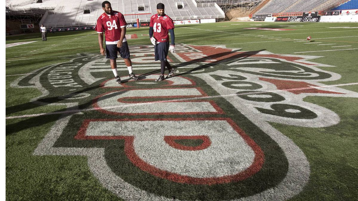 Jeff Robertshaw, left, and Guillaume Allard-Cameus of the Montreal Alouettes stand at centre field of McMahon Stadium during Wednesday's practice.
