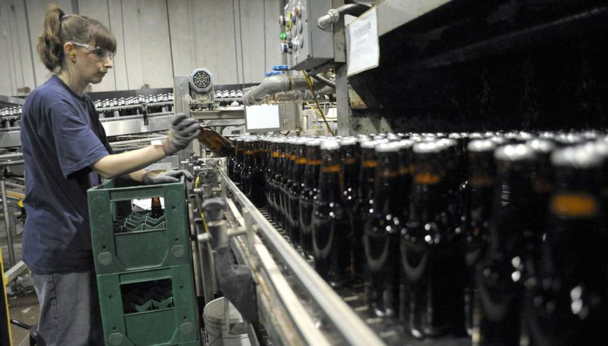 A line worker pulls out bad bottles of beer at Brick Brewing Co. in Kitchener, Ont.