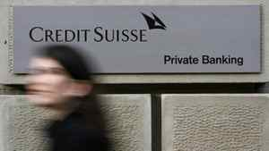 A woman walks past an office building of Swiss bank Credit Suisse at the Bahnhofstrasse in Zurich December 4, 2008.