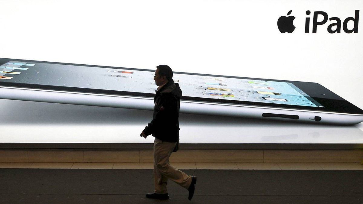 A man walks past an iPad2 advertisement in Shanghai, China, Monday Feb. 13, 2012. A Chinese company said Tuesday it will ask customs officials to ban imports and exports of Apple Inc.'s iPads due to a dispute over ownership of the trademark.