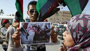 A man holds a photo Moammar Gadhafi's body as Libyan's celebrate the dictator's death in Tripoli on Oct. 20, 2011.