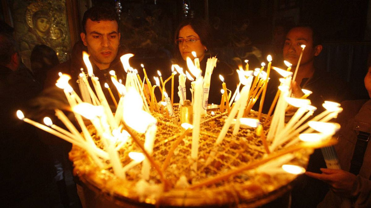 Christian worshippers light candles following Christmas day Mass at the Church of the Nativity, traditionally believed by Christians to be the birthplace of Jesus Christ, in the West Bank town of Bethlehem, Sunday, Dec. 25, 2011. Hundreds of Christian faithful, defying lashing rains and wind, celebrated Christmas Mass at Jesus' traditional birthplace on Sunday, spirits high despite the gloomy weather.