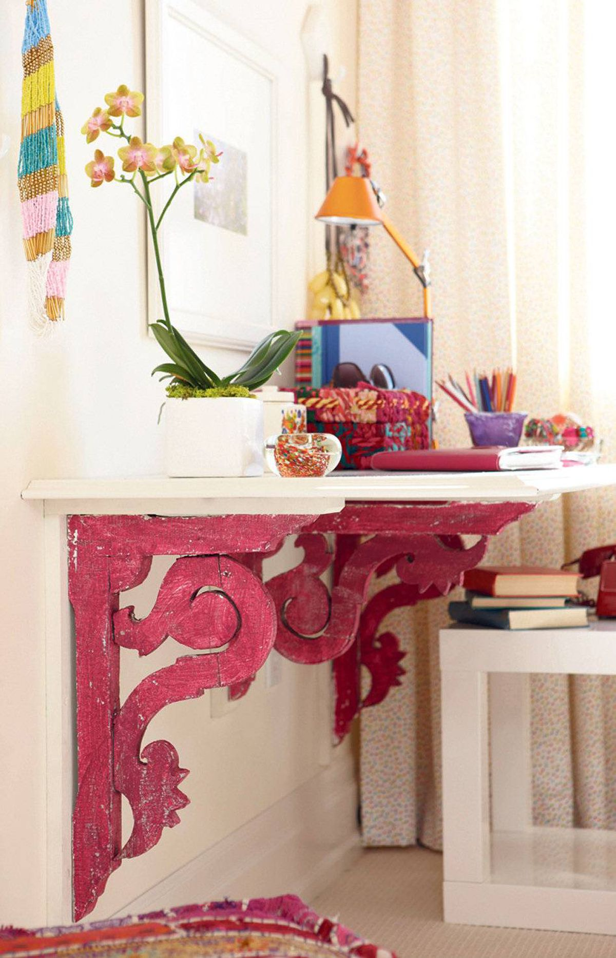 PAINT WISELY You don't need a gallon of paint to make a bold statement. Instead, target a small architectural detail, like the reclaimed brackets supporting this DIY desk. Then create a colour motif in the surrounding vignette by layering in accessories in matching tones.