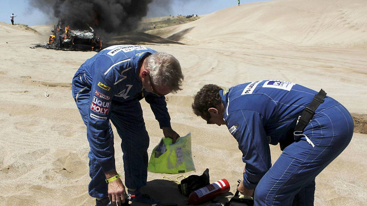 South Africa's Alfie Cox (R) and co-pilot Germany's Jurgen Schroeder arrange their gear near their burning Volvo during the first stage of the fourth South American edition of the Dakar Rally 2012 from Mar Del Plata to Santa Rosa de la Pampa January 1, 2012.