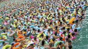 Residents crowd in a swimming pool to escape the summer heat during a hot weather spell in Daying county of Suining, Sichuan province in this file picture taken July 4, 2010.