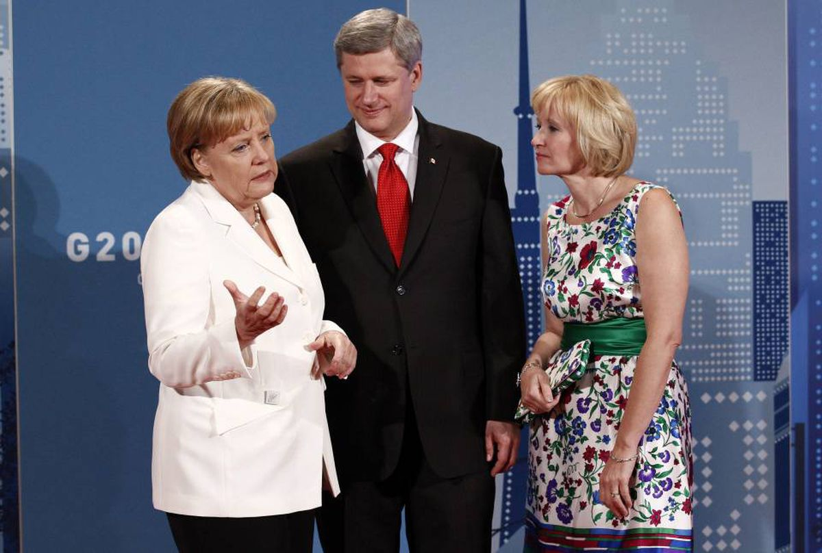 Germany's Chancellor Angela Merkel (L) is greeted by Canada's Prime Minister Stephen Harper and his wife Laureen as she arrives at the G20 Summit in Toronto, June 26, 2010.