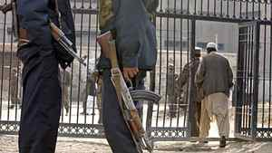Afghan security officers stand guard in front of a Kabul prison gate in 2004.