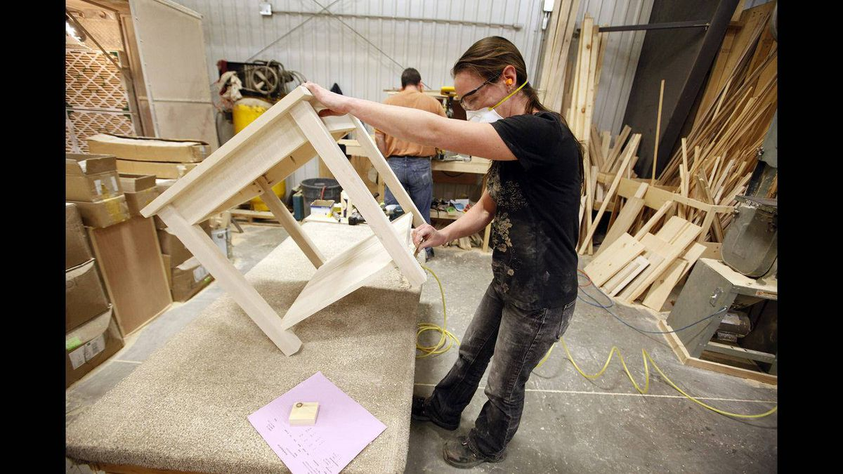 Vokes Furniture employee Michelle McMillan sands a solid wood table at the company's Shallow Lake factory.