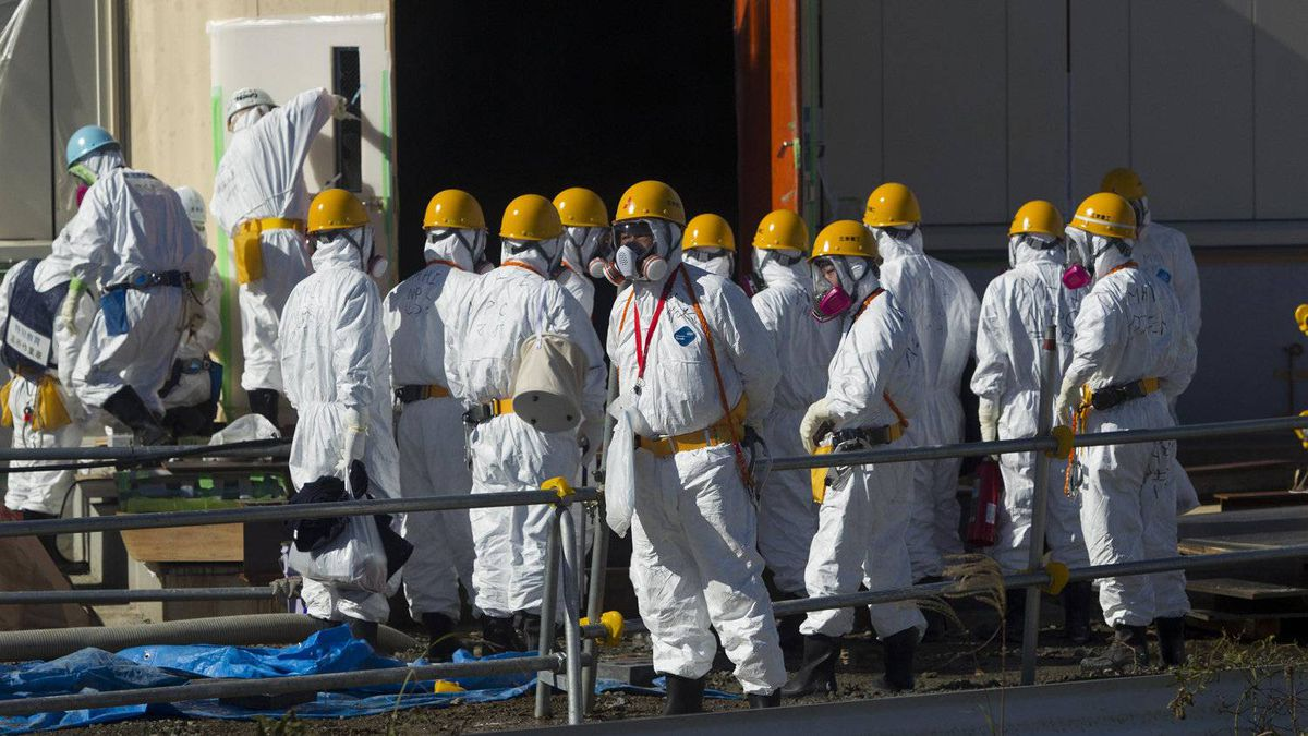 Men wearing protective suits and masks work at the crippled Tokyo Electric Power Co. (Tepco) Fukushima Dai-Ichi nuclear power station in Okuma Town, Fukushima Prefecture, Japan, on Saturday, Nov. 12, 2011. Tepco is struggling to contain the worst nuclear disaster in 25 years. Photographer: David Guttenfelder/Pool via Bloomberg