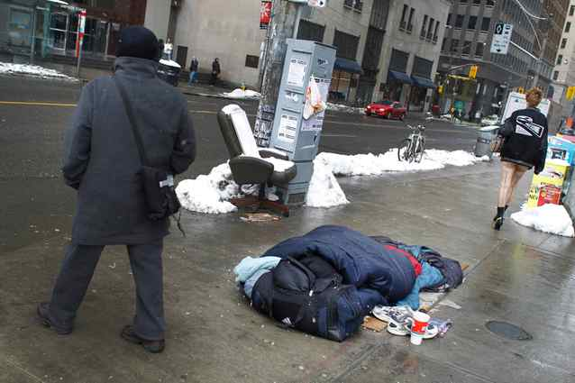 A homeless man sleeps on the southwest corner of Bay and Queen Streets.