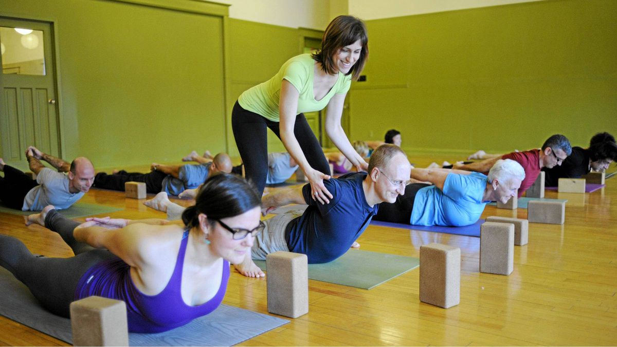 Leena Miller, a certified Anusara-Inspired yoga teacher, adjusts a student during class at her studio in Kitchener-Waterloo, Ont. Photo by Ian Willms (not Globe and Mail)