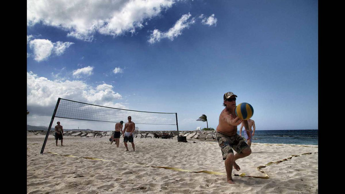 A friend stretches to keep volleyball in play, during a pick-up game of beach volleyball in. While on vacation in , Montigo bay, Jamaica.