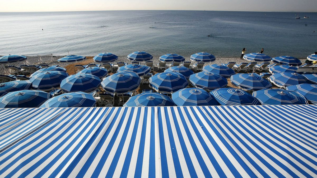 People swim in the Mediterranean Sea as blue beach umbrellas provide shade from the sun along the beach in Nice, southeastern France, Tuesday, Sept. 27, 2011.