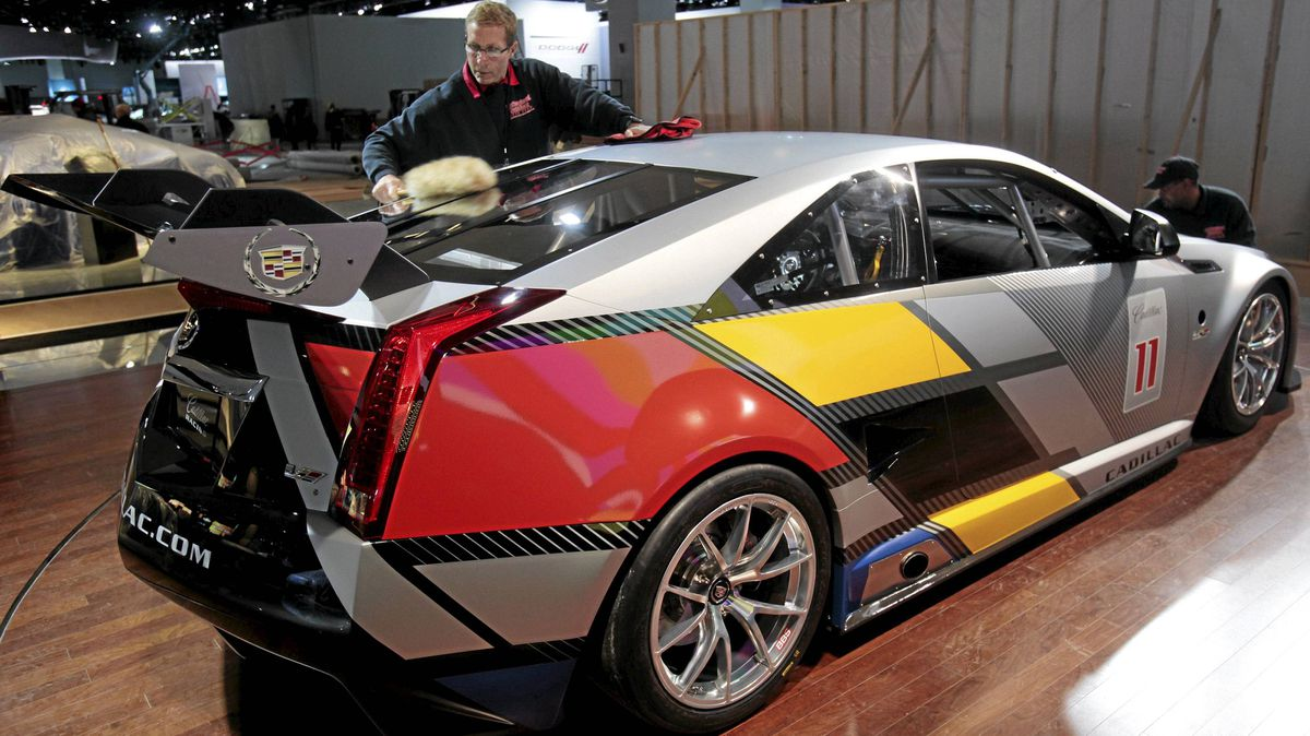 Michael Price cleans a Cadillac CTS-V coupe race car before its debut for press days at the North American International Auto show in Detroit, Michigan January 8, 2011.