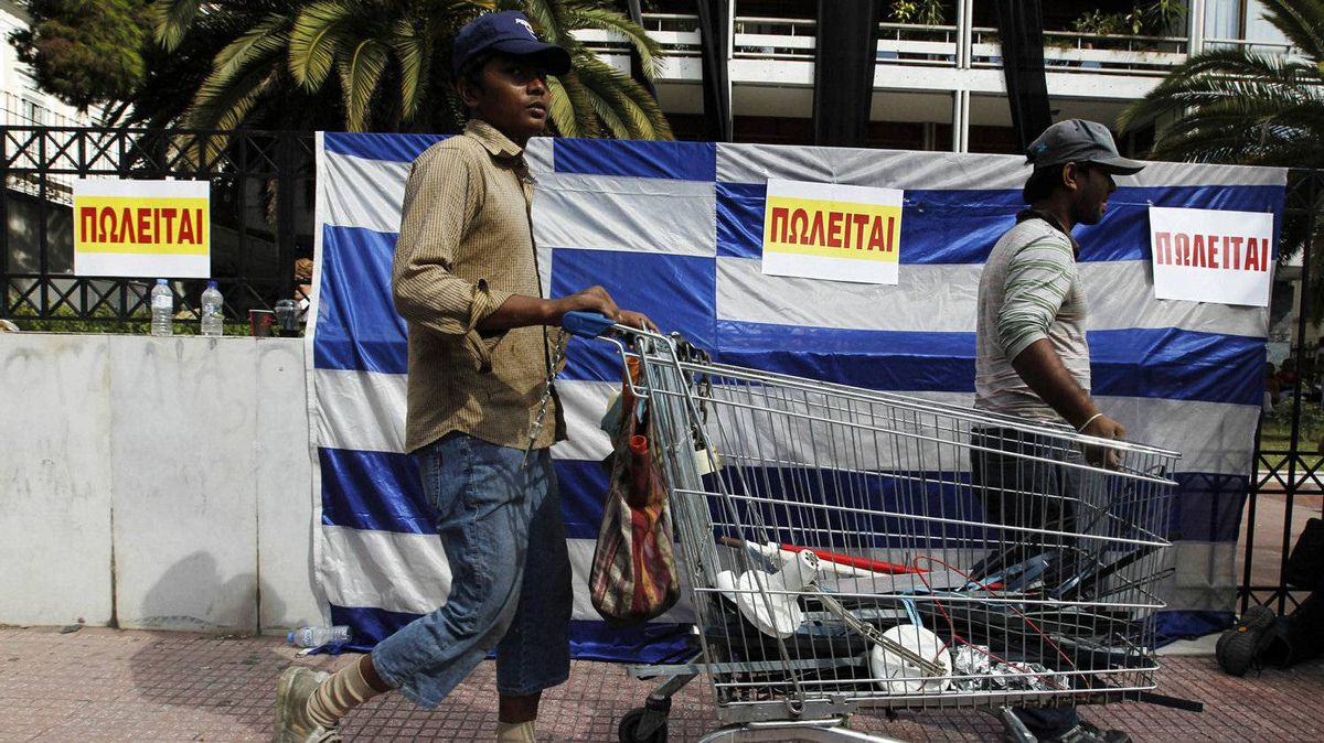 """Immigrants pass in front of a Greek flag emblazoned with """"for sale"""" signs outside the Interior Ministry building in central Athens on Sept. 29, 2011. Protesting civil servants occupied several ministry buildings, including the Finance Ministry, ahead of a visit later Thursday by international debt inspectors to decide on whether to release the next vital installment for rescue loans to debt-shackled Greece."""